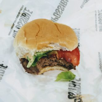 Impossible Burger in a bun with lettuce and tomato on a paper wrapper